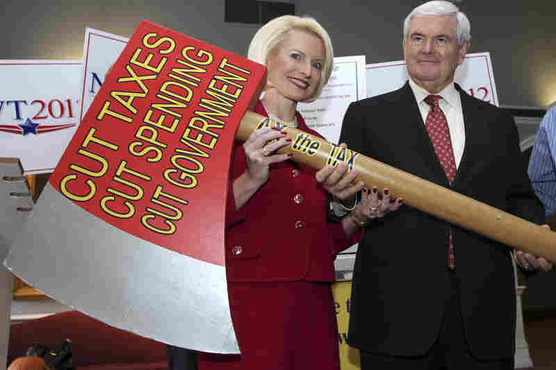 Former House Speaker Newt Gingrich, with his wife Callista, holds an oversize replica of an ax after signing a pledge to cut taxes, spending and government in Concord, N.H., on Oct. 25, 2011 during his run for the GOP nomination.