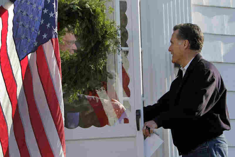 Former Massachusetts Gov. Mitt Romney shakes hands during a door-to-door campaign swing during his presidential run on Dec. 3, 2011, in Manchester, N.H.