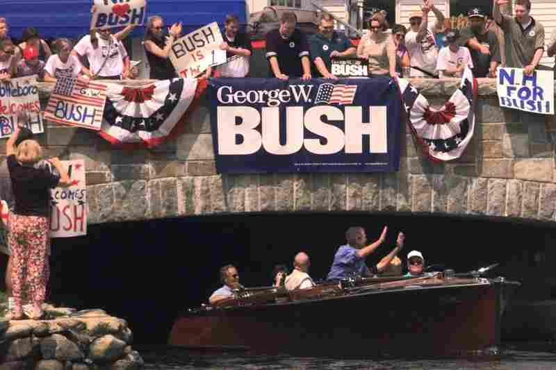 Then Gov. George W. Bush waves to supporters from a boat as he arrives on Lake Winnipesaukeein Wolfboro, N.H., July 31, 1999.