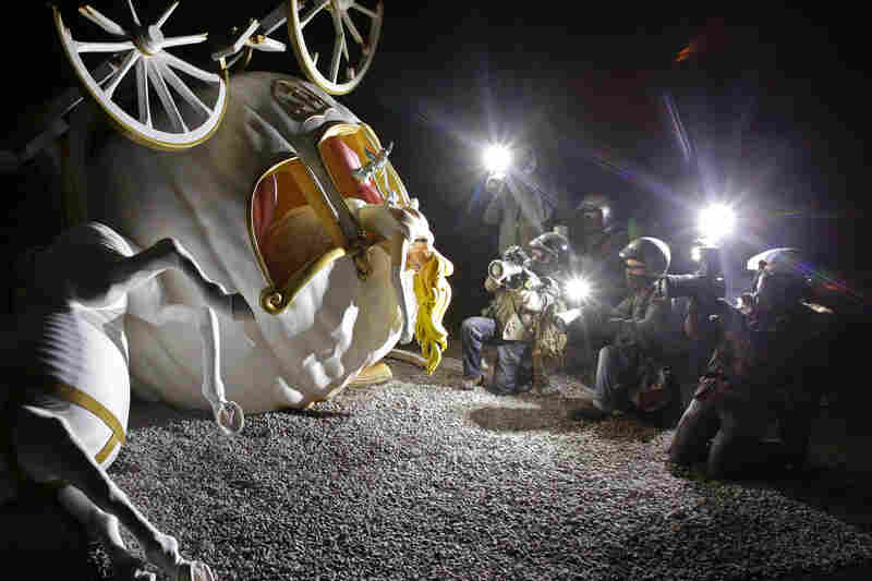 A piece featuring the character Cinderella after the crash of her pumpkin carriage, surrounded by paparazzi.