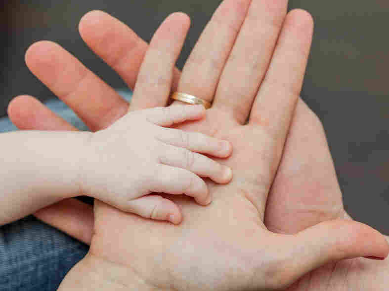 Father and mother holding child's hand.