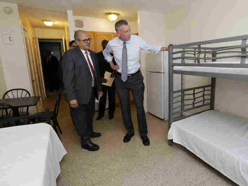 New York Mayor Bill de Blasio (right) visits a room at the Corona Family Residence, a homeless facility in the Queens borough of New York, in May.