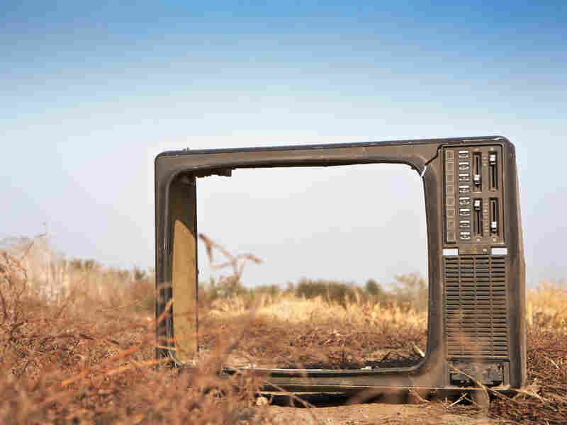 A broken television in a dried-out field.