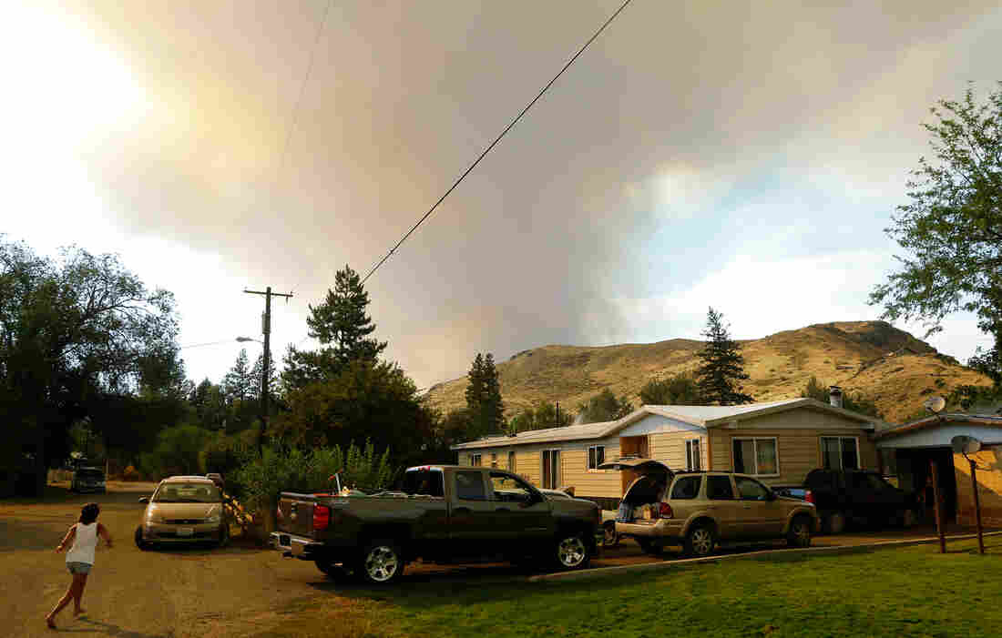 Smoke rises from a wildfire approaching Twisp, Wash., on Aug. 19. Smoke can damage the health of people hundreds of miles downwind.