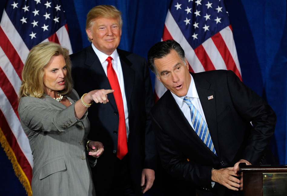 Mitt Romney peers over the podium at guests being pointed out by his wife, Ann, during an event at which Donald Trump endorsed Romney in 2012. (Ethan Miller/Getty Images)