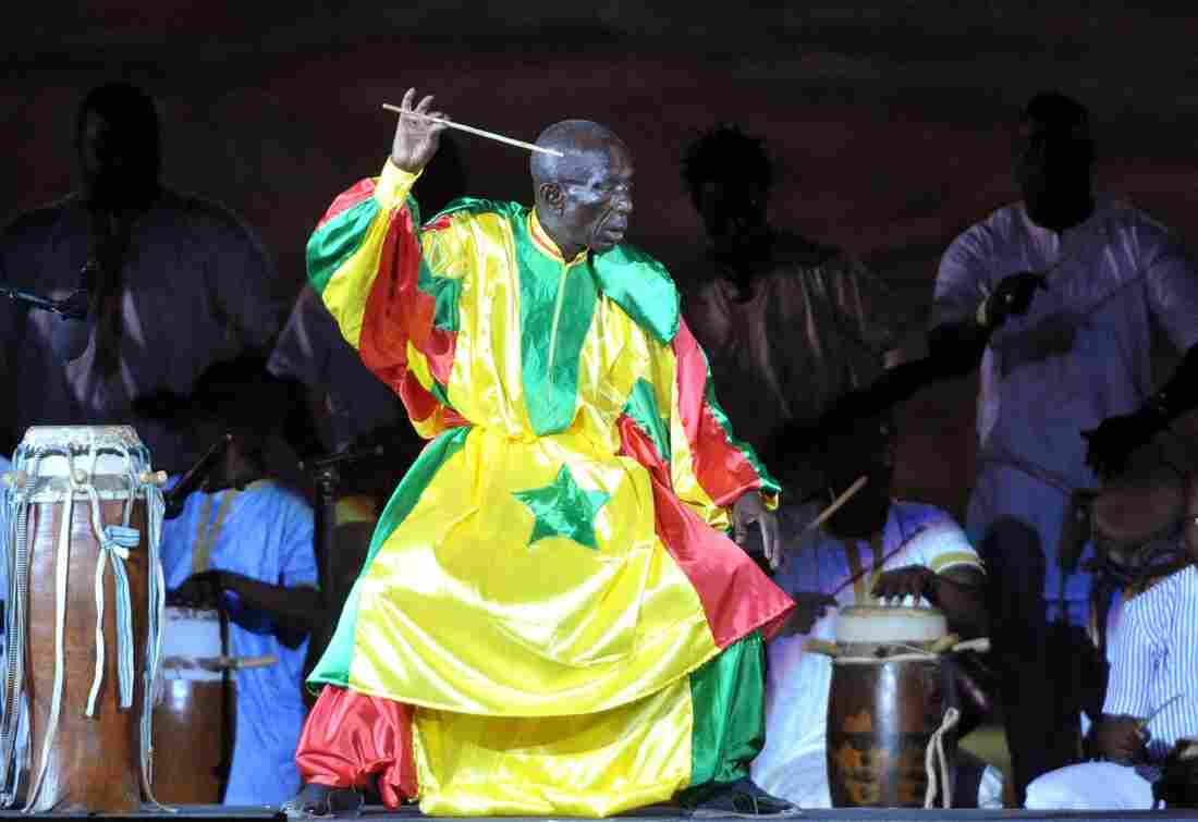 Doudou N'Diaye Rose was a brilliant musician and a brilliant dresser as well, with a custom-made wardrobe of vivid, billowing outfits. Above, wearing Senegal's national colors, he sets the beat at a concert in Dakar on Dec. 10, 2010.