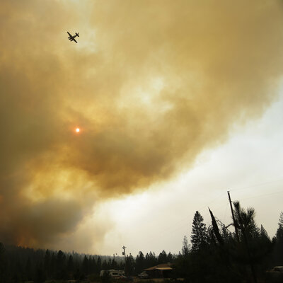 An airplane used to fight wildfires flies over a blaze that flared up near Omak, Wash., on Thursday.