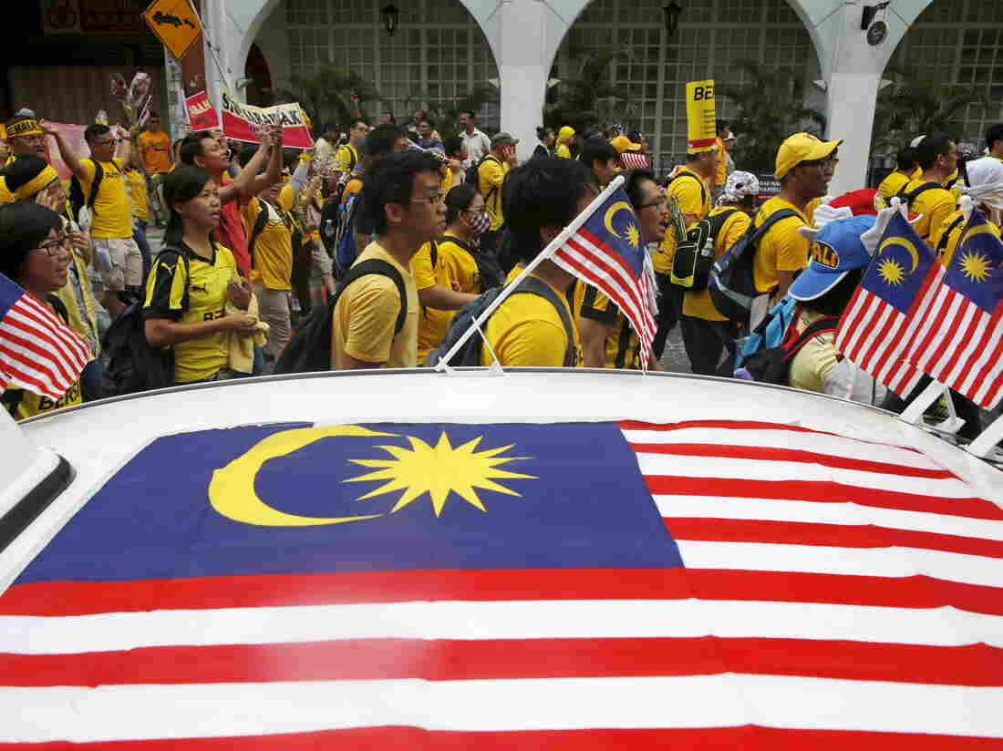 "Supporters of pro-democracy group ""Bersih"" (Clean) pass a taxi decorated with Malaysian flags as they march toward Dataran Merdeka in Malaysia's capital city of Kuala Lumpur, on Saturday. The group is protesting alleged corruption at the top levels of government."
