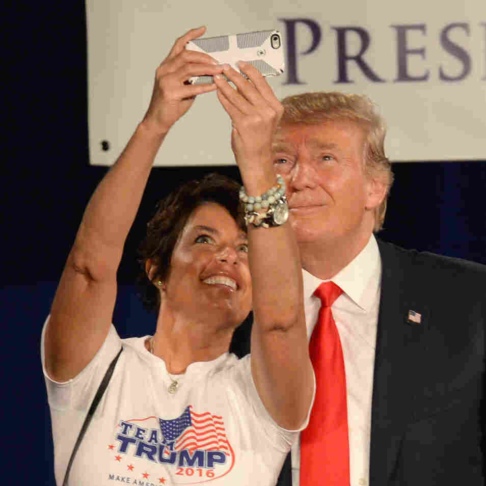 """Donald Trump poses for a selfie with a woman wearing a """"Team Trump"""" T-shirt on stage at the National Federation of Republican Assemblies Presidential Preference Convention in Nashville, Tennessee."""