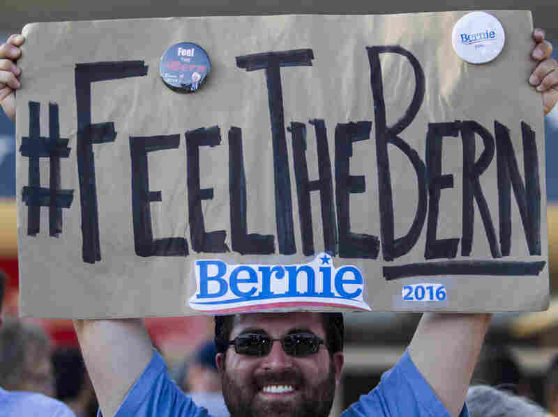 """Frank Rothstein holds a """"Feel the Bern"""" sign before a rally Bernie Sanders in Los Angeles that drew tens of thousands. The phrase has become an anti-establishment rallying cry for Sanders fans."""