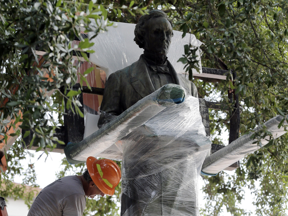 Workers wrap protective materials around a statue of Confederate President Jefferson Davis as they prepare to move the sculpture on the University of Texas campus in Austin, on Sunday. (Eric Gay/AP)