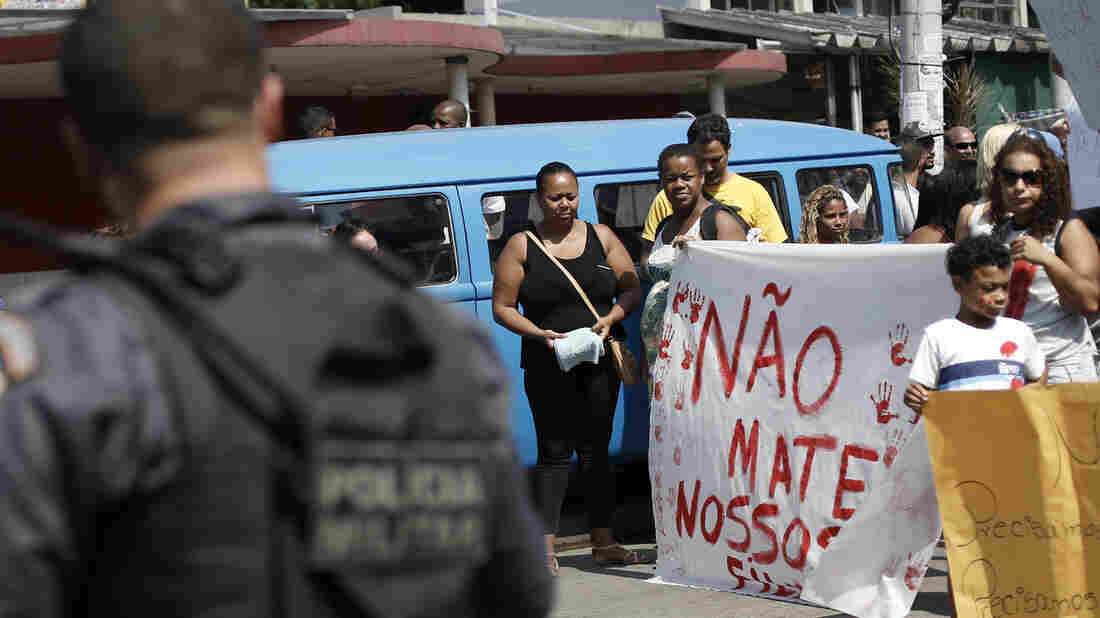 """Protesters hold a sign Saturday that reads, in Portuguese, """"Don't kill our children,"""" in a march against police and gang conflicts that have left residents of the Complexo de Alemao favela in the crossfire."""