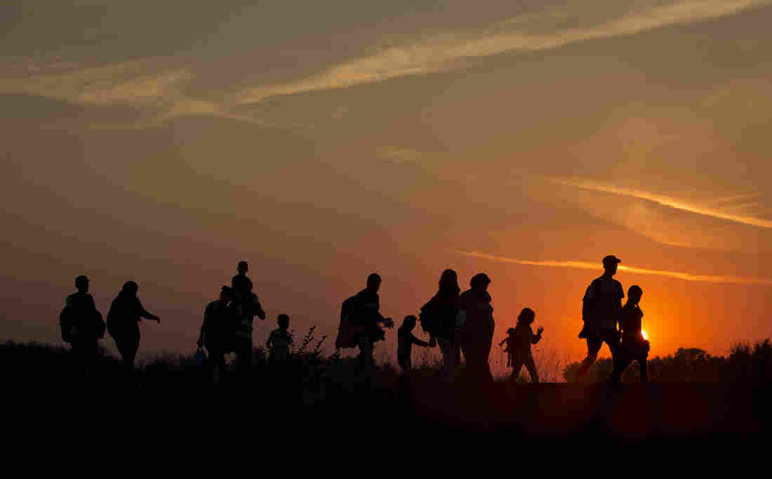 Refugees from the Middle East are silhouetted against the setting sun as they walk on railway tracks from Serbia, in Roszke, Hungary, on Sunday.