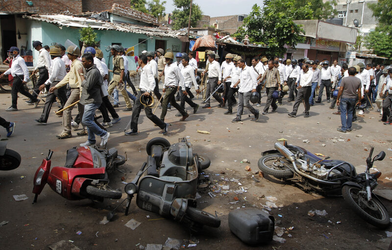 Indian policemen in plain clothes walk past vehicles damaged during a clash between two groups in Ahmadabad, India, Tuesday, Aug. 25, 2015. Clashes were reported in parts of the city after tens of thousands of members Gujarat's Patel community held a rally demanding affirmative action for better access to education and employment.