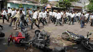 Indian police in plain clothes walk past vehicles damaged during a clash after the Aug. 25 rally led by Hardik Patel.