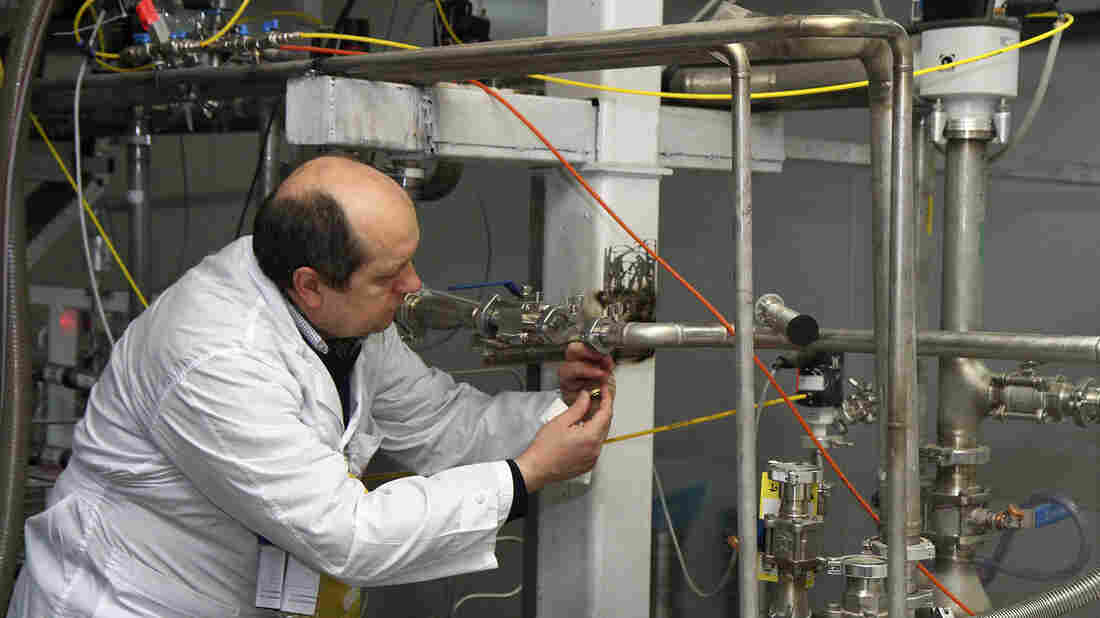 An International Atomic Energy Agency inspector cuts a uranium enrichment connection at Iran's Natanz facility, 200 miles south of Tehran, in 2014. The U.S. Congress is expected to address the Iranian nuclear deal this month. One unresolved issue: How much work might Iran have done previously on weaponizing its program?