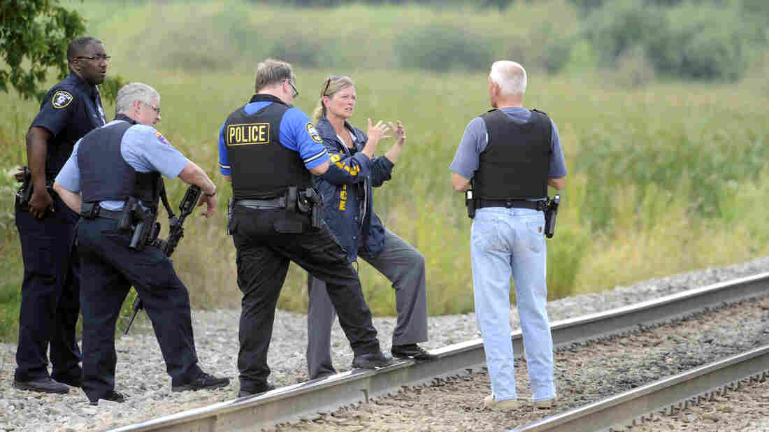 Police officers confer while searching for three suspects in Tuesday's shooting death of a police officer near Fox Lake, Ill., about 50 miles north of Chicago.