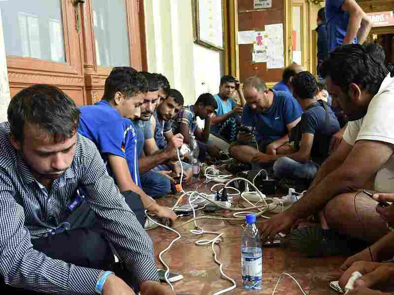 Migrants charge their cellphones at Keleti Railway Station in Budapest, Hungary, on Thursday.