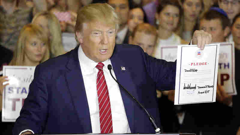 Republican presidential candidate Donald Trump holds a signed pledge during a news conference in Trump Tower, Thursday, Sept. 3, 2015 in New York.