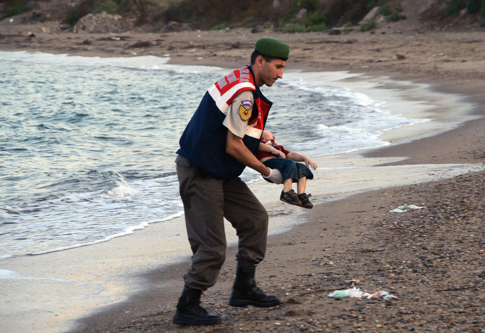 A Turkish paramilitary police officer carries the body of 3-year-old Aylan Kurdi, found washed ashore near the Turkish resort of Bodrum early Wednesday. The boats carrying the boy's family to the Greek island of Kos capsized. His 5-year-old brother and mother also lost their lives. (DHA/AP)