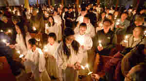 Vietnamese-Americans light candles at St. Helena, a Catholic church in Philadelphia, on April 4. Like many other once-struggling churches, St. Helena has been revitalized by immigrant parishioners. About 200 Vietnamese families worship at this church, along with others from Latin America, the Philippines and Africa.
