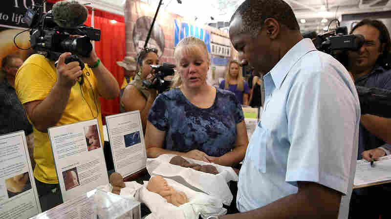 """Carson looks at a display of fetus models at the """"Iowa Right to Life"""" booth at the Iowa State Fair."""