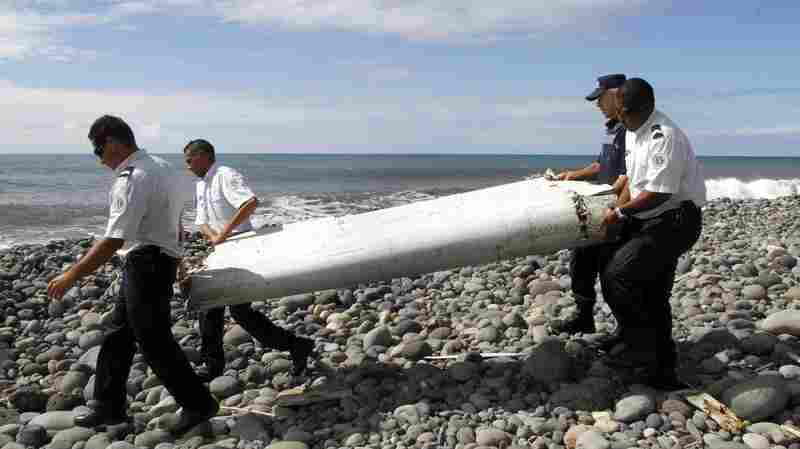 French officers carry a wing fragment, called a flaperon, that washed ashore on La Réunion island in the Indian Ocean on July 29.