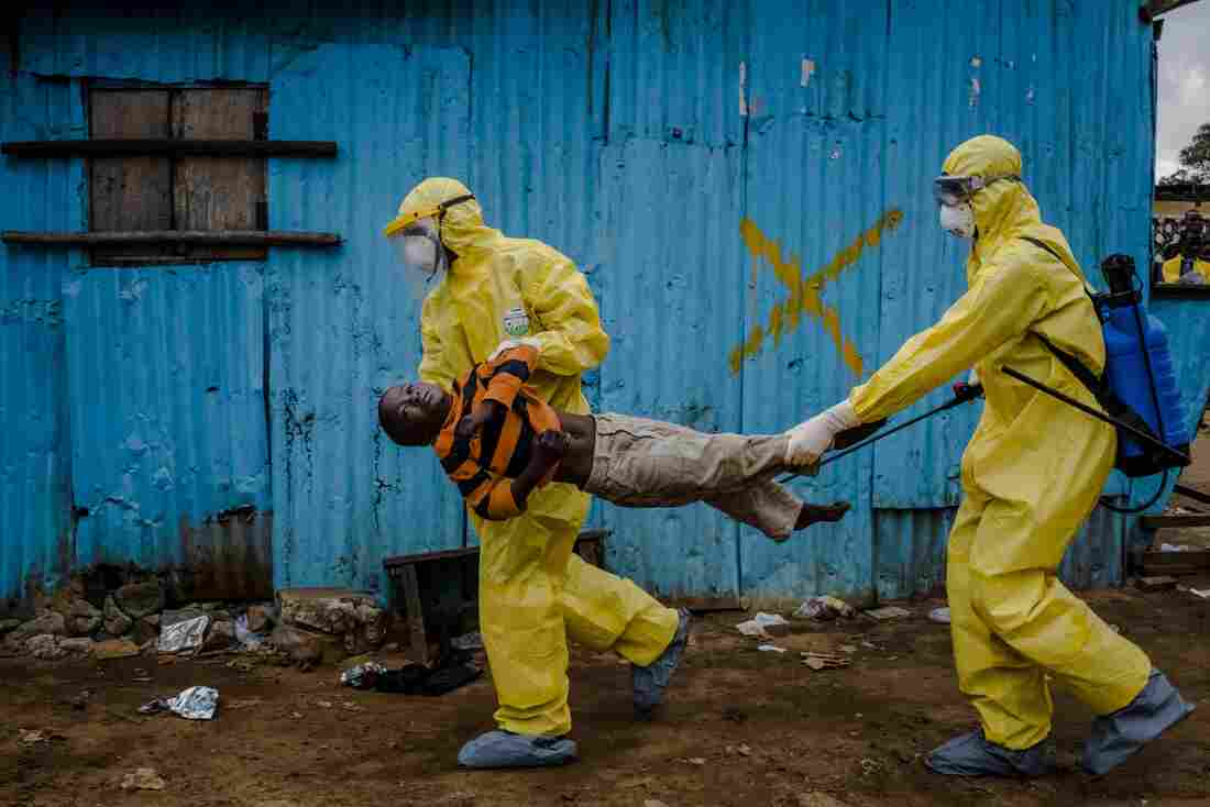 James Dorbor, age 8, was suspected of having Ebola. Medical staff in protective gear carried him into a treatment center on Sept. 5, 2014, in Monrovia, Liberia.