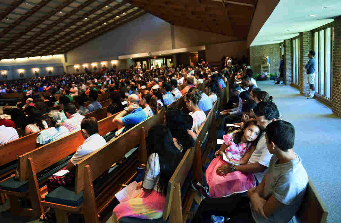 Rocio Cruz (facing camera), 7, sits with her father, Jose Carlos Cruz, during a Spanish Mass at Good Shepherd Catholic Church last month in Alexandria, Va. Hispanics account for 34 percent of American Catholics.