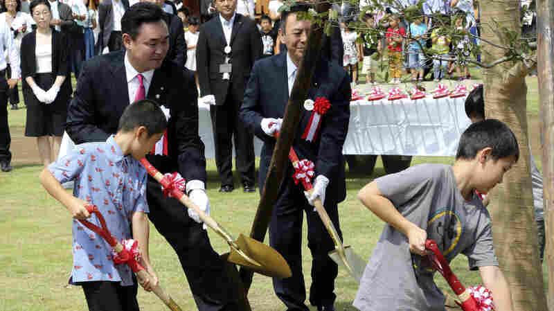 Noraha Mayor Yukiei Matsumoto, rear left, plants a tree with children of Naraha residents during an event in Naraha, Fukushima, northern Japan, on Saturday.