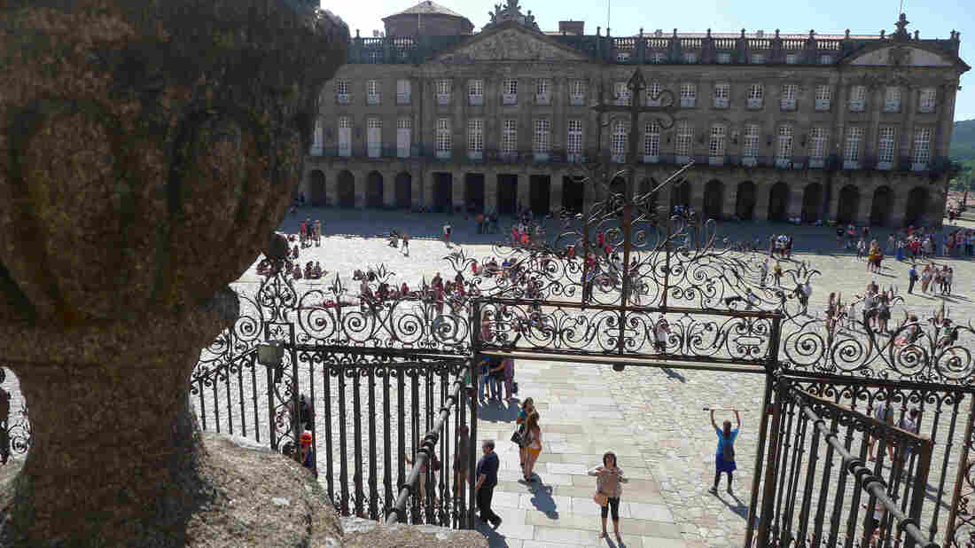 Hikers on the Camino de Santiago, Spain's most famous pilgrimage path, celebrate their journey's end in the plaza in front of the cathedral of Santiago de Compostela.