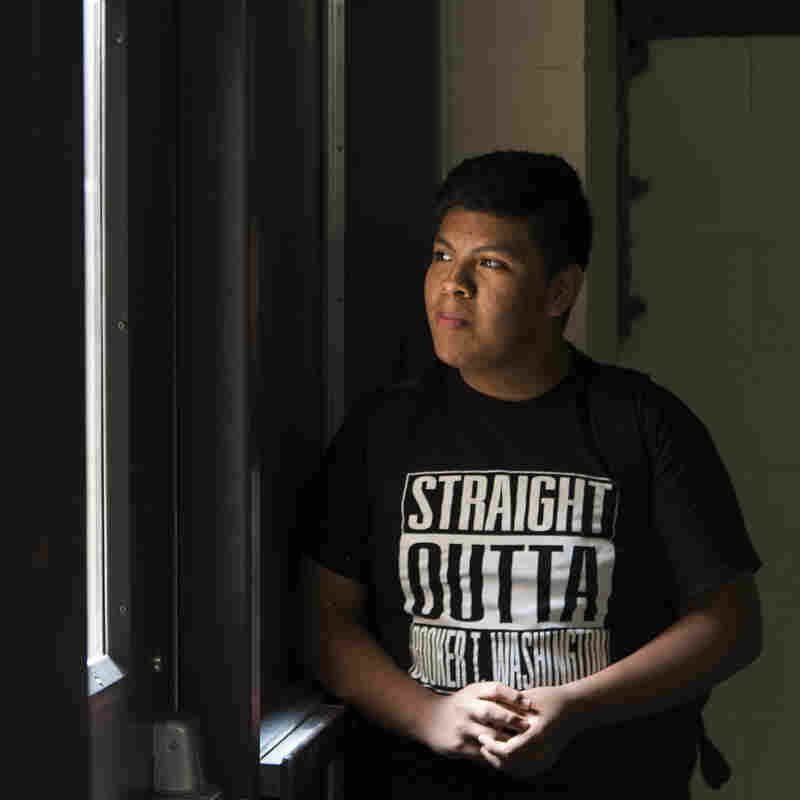 Jose Arriaga waits for his friends under the stairs at the end of the school day at Booker T. Washington High School. Jose began his freshman year this semester.