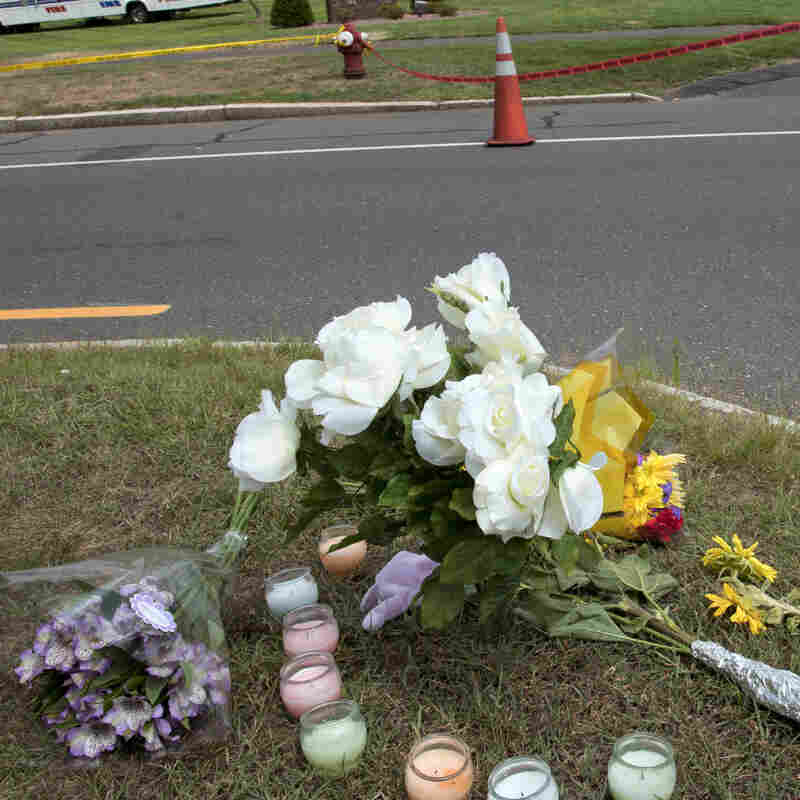 Flowers and candles are set up as a memorial in front of the entrance to Hartford Distributors following a shooting Aug. 4, 2010, in Manchester, Conn. Eight employees were killed by a former worker.