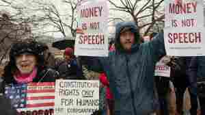 Demonstrators march in the snow outside the White House during a rally against the Supreme Court's decision five years ago in favor of Citizens United, which allows private citizens and corporations to make unlimited donations for political campaigns.