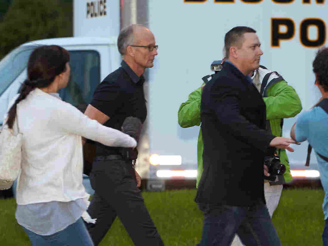 Dentist and trophy hunter Walter Palmer (left) walks to his clinic in Bloomington, Minn., with private security and members of the media Tuesday.