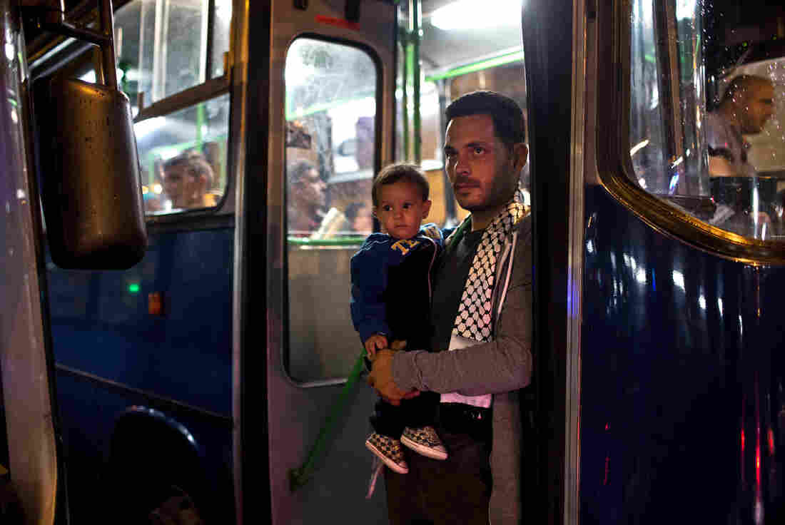 A man and a child stand in the doorway of a bus provided by Hungarian authorities for migrants and refugees stranded at the Keleti train station in Budapest, Hungary, on Saturday. The migrants boarded buses provided by Hungary's government and headed to Austria, which allowed them in.