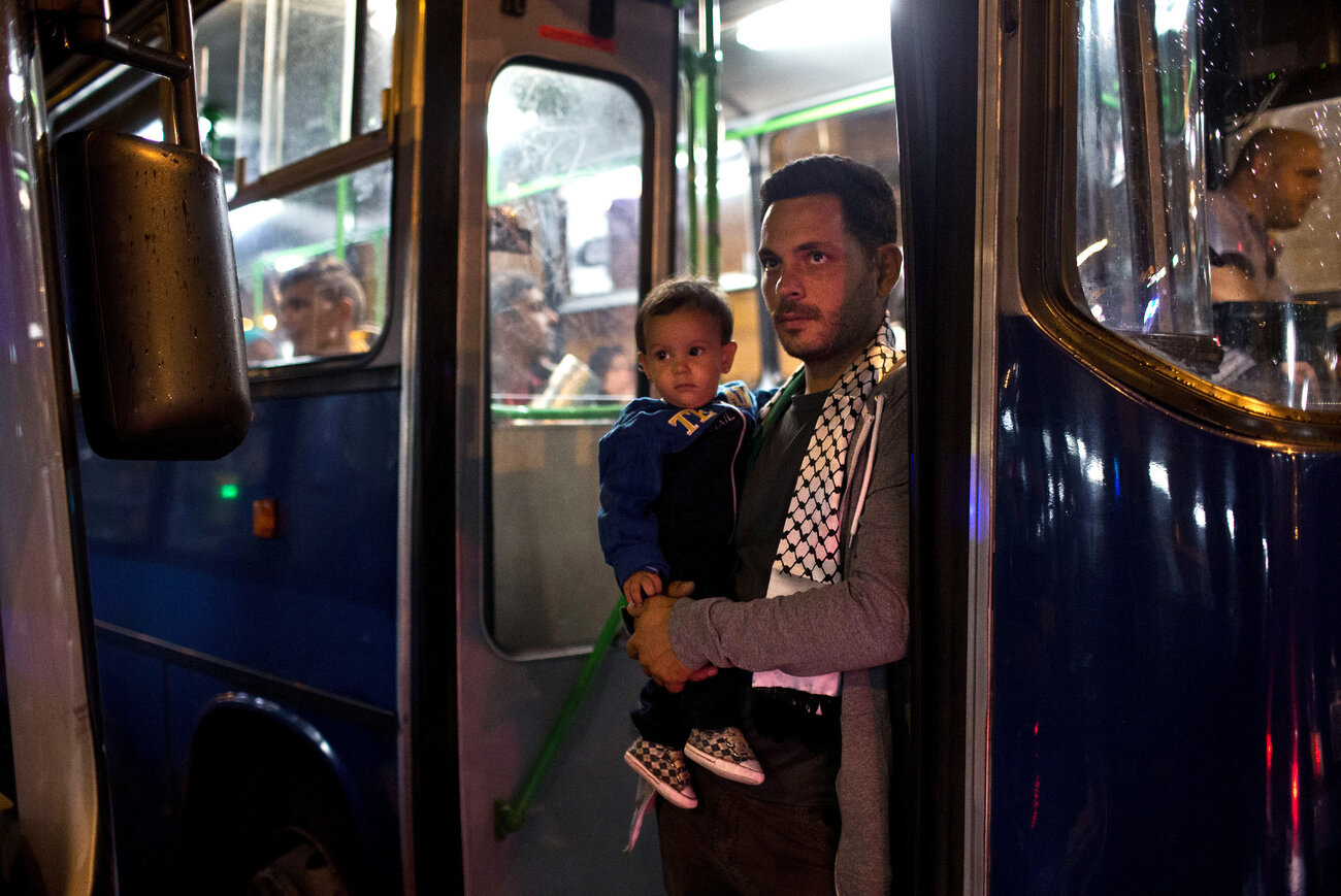 A man and a child stand next to the door of a bus provided by Hungarian authorities for migrants and refugees stranded at the Keleti train station in Budapest, Hungary, on Sept. 5, 2015. The migrants boarded buses provided by Hungary's government and headed to Austria, which allowed them in.