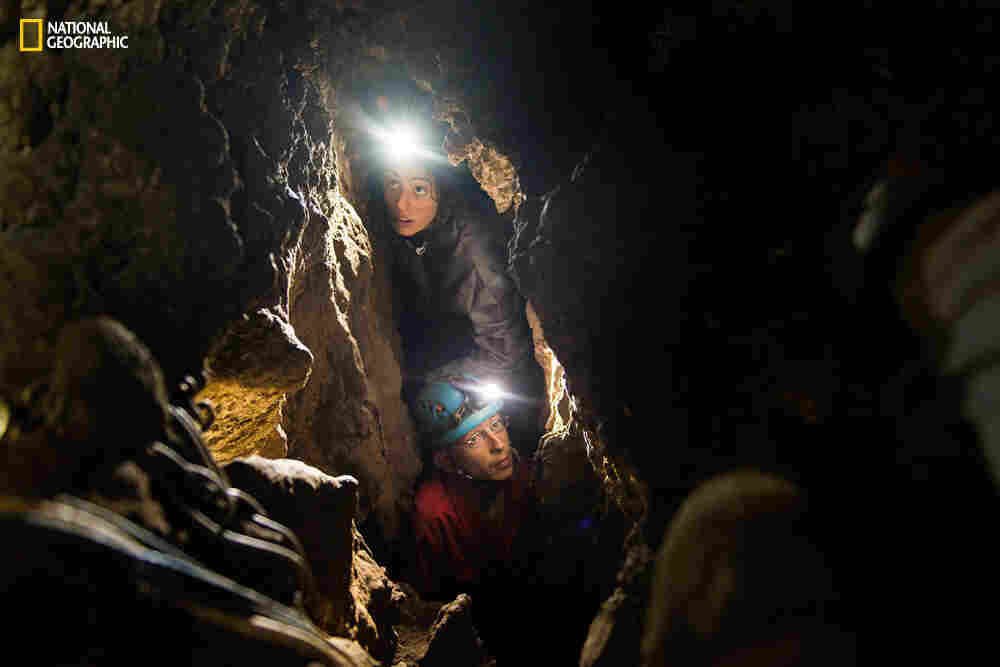 Anthropologist Lee Berger's daughter, Megan (top), and Rick Hunter, a member of the underground exploration team, navigate the narrow chutes leading to the Dinaledi Chamber of the Rising Star cave in South Africa. That's where fossilized bones belonging to H. naledi, a new species related to humans, were discovered.