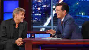 New Late Show host Stephen Colbert (right) talks with actor George Clooney.