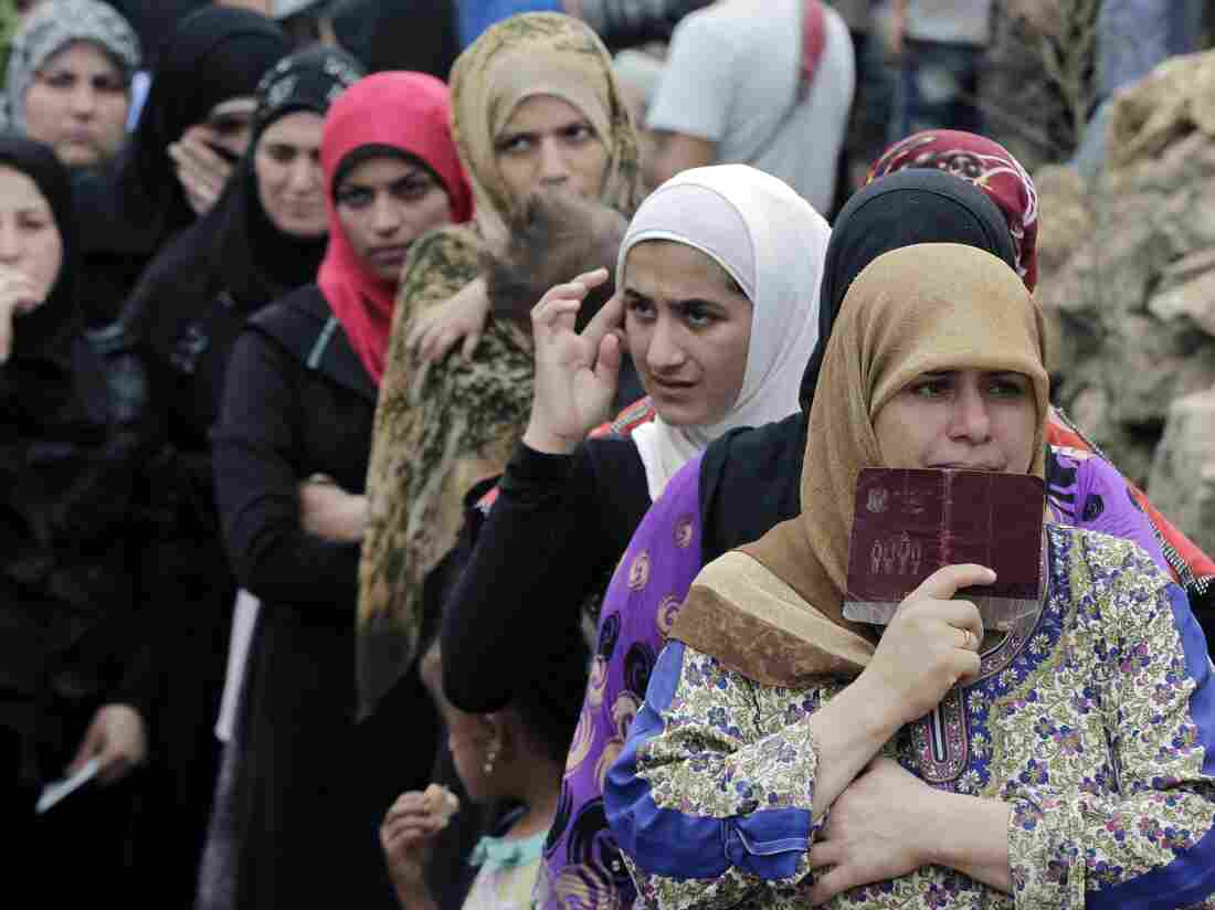 Syrian women wait to receive aid at a refugee camp in the Lebanese town of Ketermaya. Lebanon has taken in 1.1 million Syrian refugees. The U.N. refugee agency says Arab Gulf states have taken none.