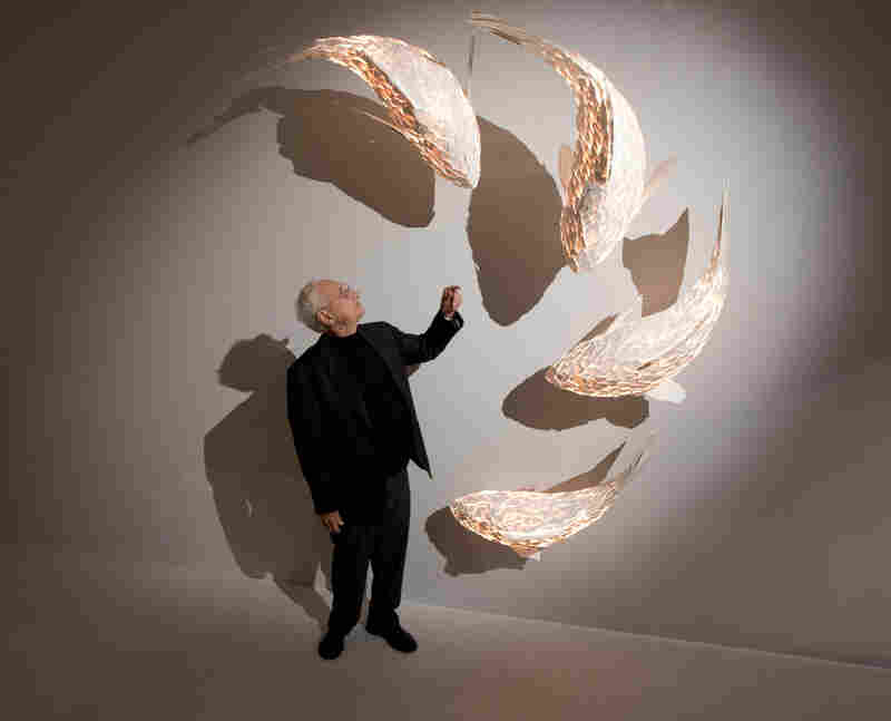 Gehry stands next to his fish lamps at the opening of an exhibition in London in 2013. As a child, Gehry used to watch carp swim in his grandmother's bathtub, before they got turned into gefilte fish.