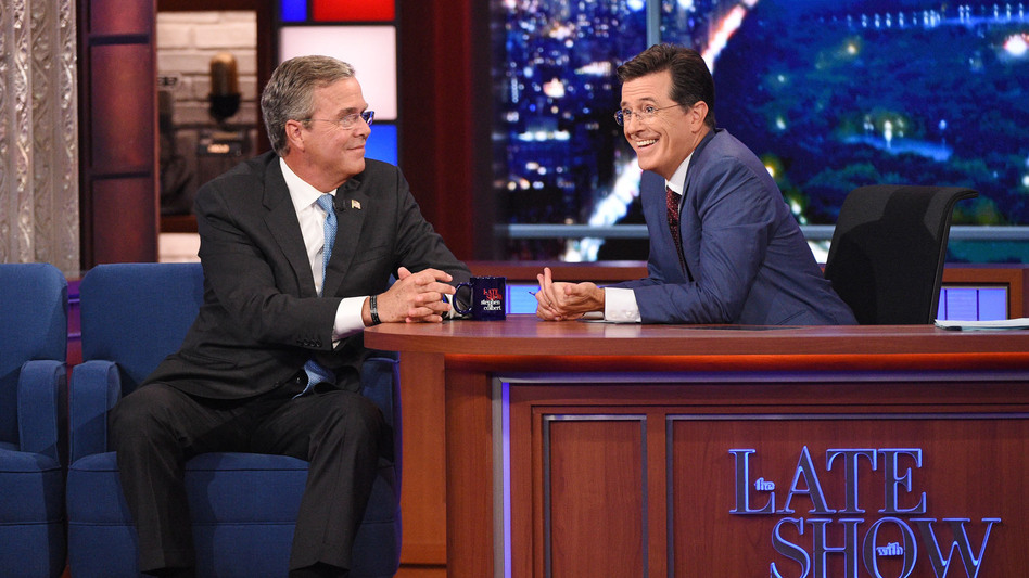 Stephen Colbert talks with Jeb Bush during Colbert's debut as <em>Late Show</em> host. The Republican presidential candidate and actor George Clooney were guests on the show. (Jeffrey R. Staab/AP)