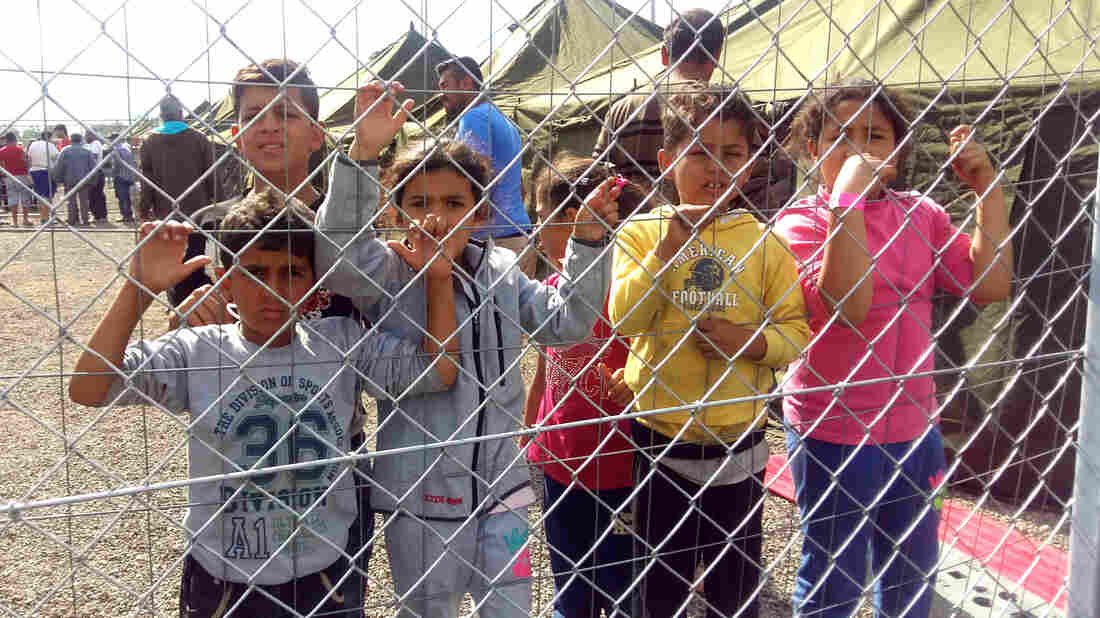 Refugee children from Syria stand behind a fence where they and their families are being detained temporarily in Hungary, near the border with Serbia. Many want to go to Germany, which has been welcoming to those seeking asylum.