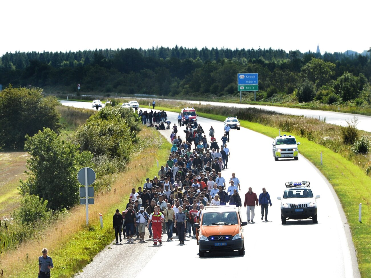 Migrants, mostly from Syria and Iraq, set out on foot along a highway on the Danish-German border, heading north to Sweden on Sept. 9. The migrants arrived that morning on a train from Germany.