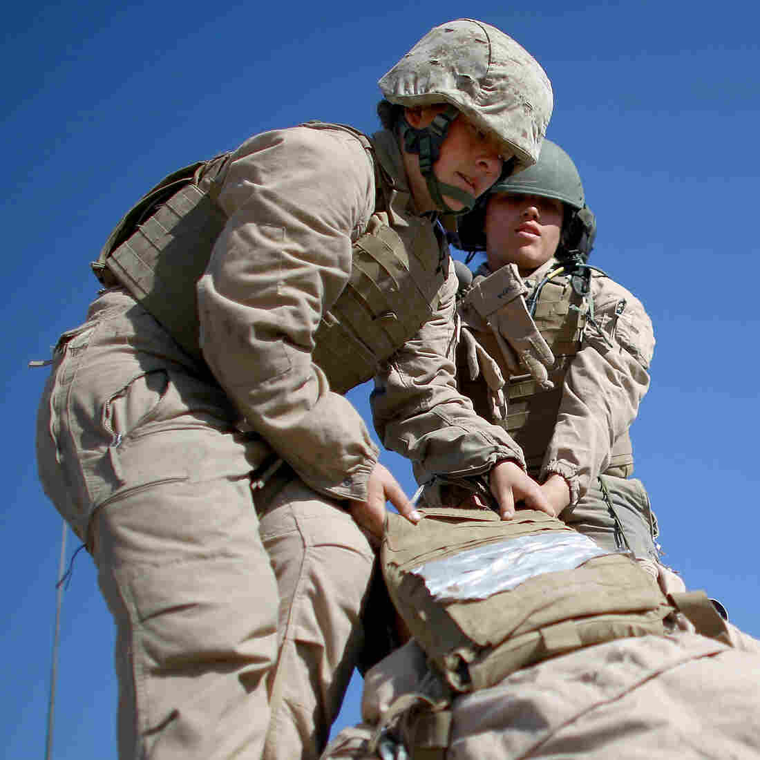 """Marine Lance Cpls. Julia Carroll (left) and Paula Pineda lift """"Carl"""" — a 220-pound test dummy — during training in March in California. Female Marines have completed months of training and are now waiting to hear whether they will be allowed to serve in combat roles."""