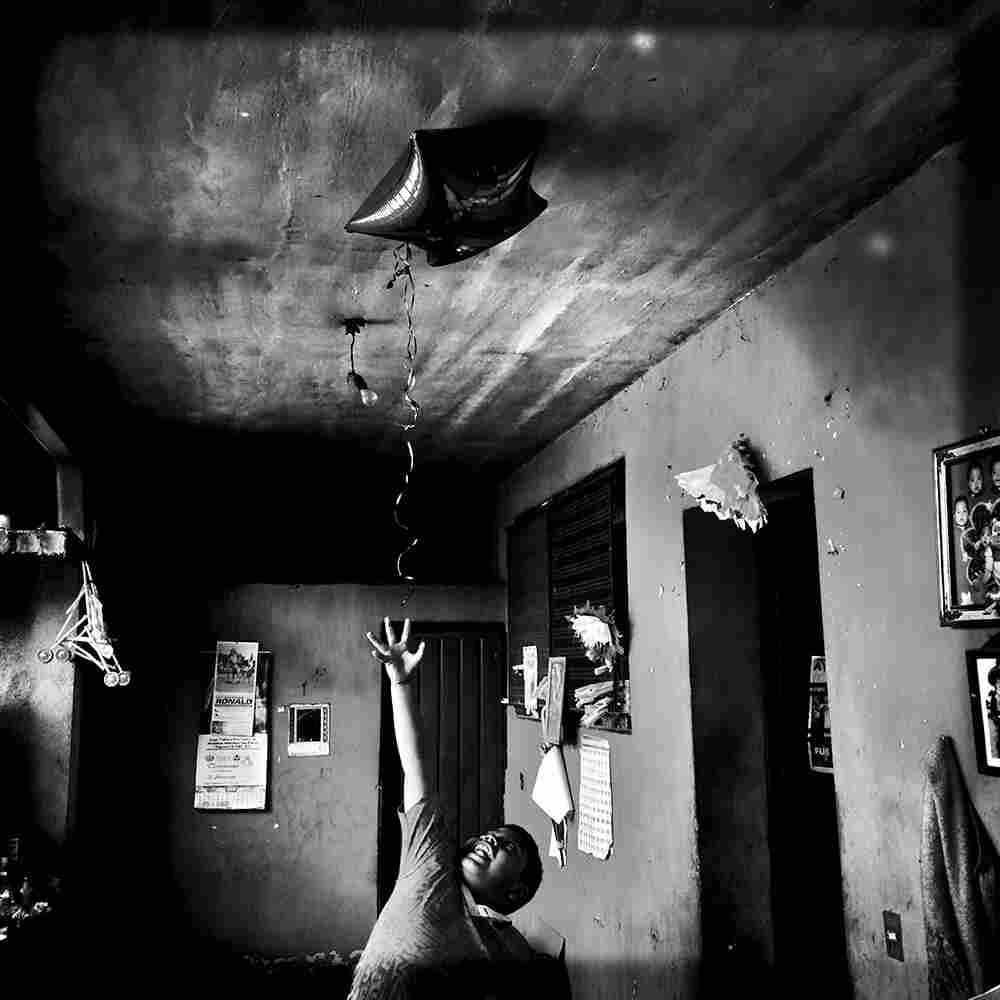 Angel, 8, tries to grab the star balloon his aunt had just brought home from work. Angel's dad is one of the 43 students missing in Mexico.