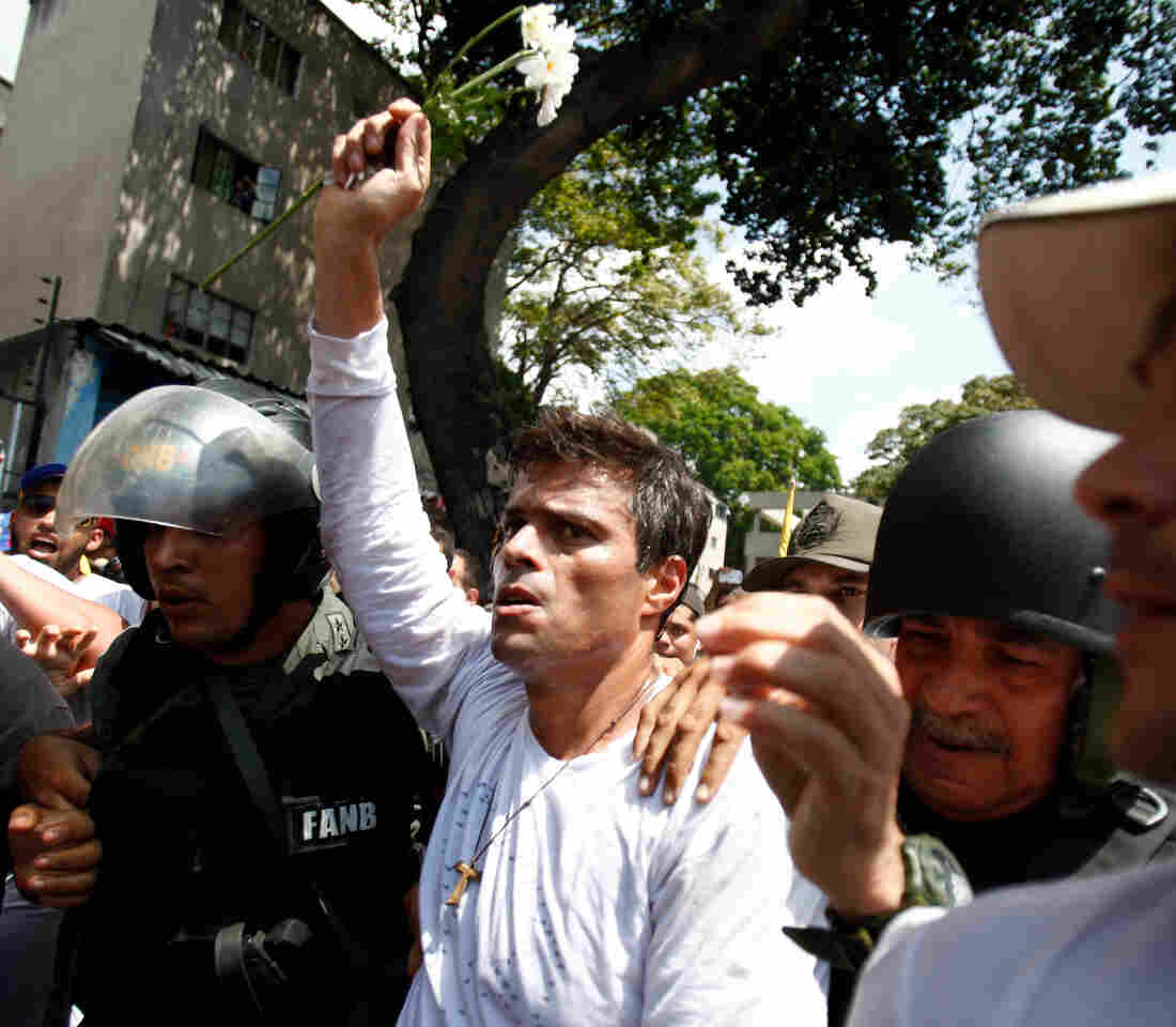Opposition leader Leopoldo Lopez is flanked by Bolivarian National Guards after Lopez after surrendering in 2014.