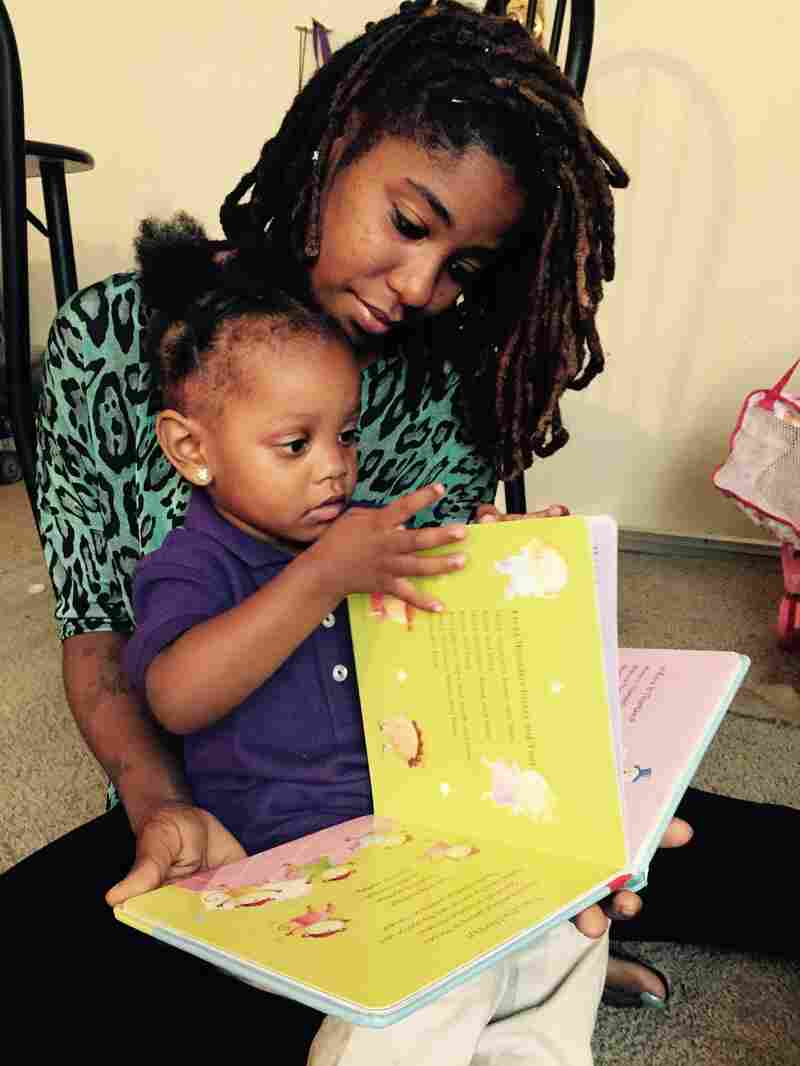 Angalene Brown and her 2-year-old daughter, Alayyah, read together in her apartment in Washington, D.C., which she recently obtained with the help of Catholic Charities of the Archdiocese of Washington.