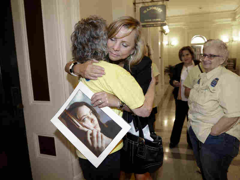 Debbie Ziegler holds a photo of her daughter, Brittany Maynard, as hugs supporter Ellen Pontac after a right-to-die measure was approved by the state Assembly on Wednesday in Sacramento, Calif.