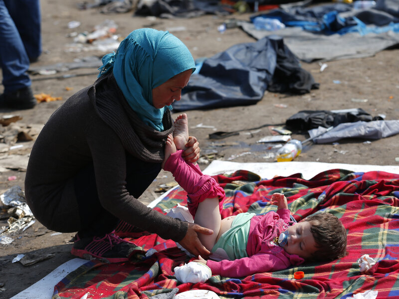 A migrant takes care of her baby at a collection point near the Serbian Hungarian border in Roszke, Hungary, on Saturday.
